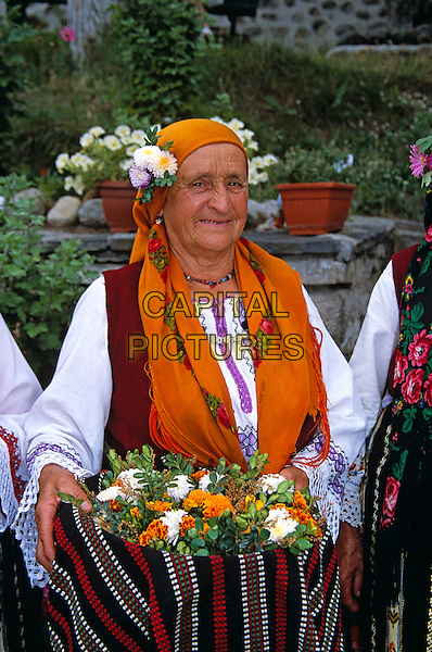 Dobarski Babi Folk Group, Dobarsko, Bulgaria, Member of folk group holding flowers