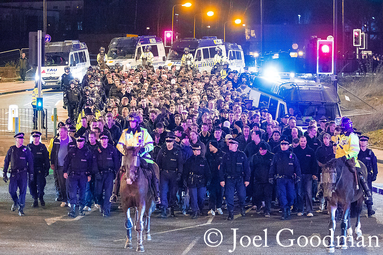"© Joel Goodman - 07973 332324 . 23/02/2012 . Manchester , UK . A large number of police contain about 150 travelling Ajax fans and lead them on foot through Manchester and Salford to Old Trafford , closing roads to traffic as they go . The fans chant ""Amsterdam hooligans"" as they go . This ahead of Manchester United hosting Ajax Europa at Old Trafford in the UEFA cup . Photo credit : Joel Goodman"