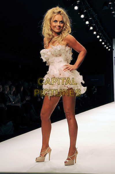 GERI HALLIWELL.The Fashion For Relief Haiti 2010 show for London Fashion Week Autumn/Winter 2010 at Somerset House, London, England..February 18th, 2010.LFW catwalk runway full length white strapless dress feathers hands on hips .CAP/CAS.©Bob Cass/Capital Pictures.