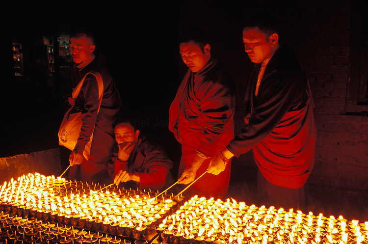 Buddhist lights and monks lighten candles for prayer ceremony at Bodhnath Stupa ..
