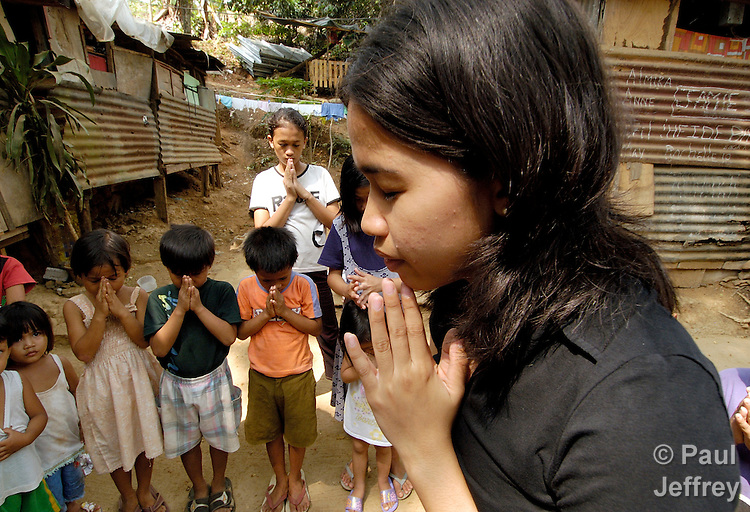 A deaconess studying at Harris Memorial College works with children in a poor neighborhood of Manila, where she teaches them to pray.