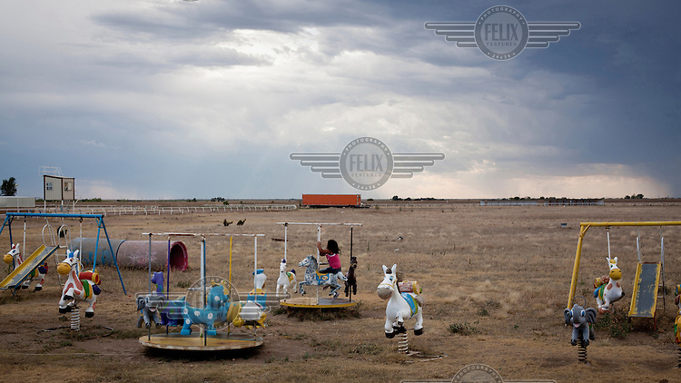 A child rides on a mini merry-go-round in a playground in Dodge City, Kansas. The area is home to many migrant workers who have come to the town to work in its meat packing plants. Kansas dominates the American beef industry, producing 25% of all beef raised in the USA. However, the industry is heavily dependent on cheap immigrant labour.