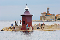Harour entance with people relaxing and fishing off the harbour wall. Piran , Slovenia