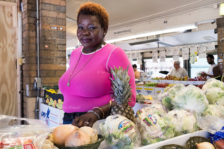Cassandra Mayfield, originally from Houston, Tex., moved to Cleveland 5 months earlier and works at a fruit stand for Egyptian immigrant Morad Botros Makar, who immigrated to the US 8 months ago. The fruit stand is located at Cleveland's West Side Market.