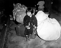 A young evacuee of Japanese ancestry waits with the family baggage before leaving by bus for an assembly center in the spring of 1942.  California, April 1942.  Clem Alberts. (WRA)<br /> Exact Date Shot Unknown<br /> NARA FILE #:  210-G-2A-6<br /> WAR & CONFLICT #:  778