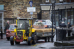 © Joel Goodman - 07973 332324 . 6 December 2013 . Marple , UK . The tractor and coffin navigate through traffic in Marple Bridge . The funeral of farmer Bob Watson . His son David Watson drives his father's coffin on a trailer hooked to the back of Bob's favourite tractor through Marple via Bob's local pub before taking it on to the church . Photo credit : Joel Goodman
