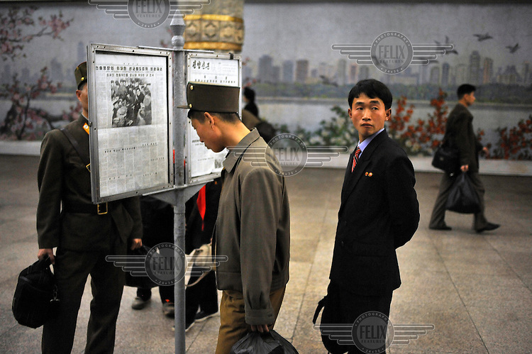 A soldier reads a newspaper posted up in one of the two Pyongyang metro stations that are open to foreign visitors.
