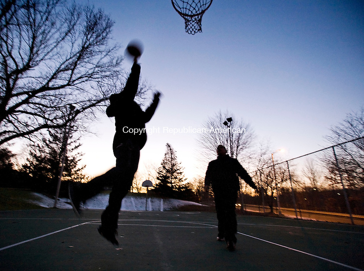 WATERBURY, CT--31 December 07--123107TJ01 - Christian Delanuece, 19, puts up a shot as Justin Perez, 13, both from Waterbury, watches during some one-on-one action at Chase Park at sunset on Monday, December 31, 2007. T.J. Kirkpatrick/Republican-American