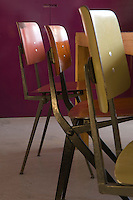 Detail of three 1950's-style stacking chairs lined up at the table
