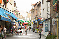 The shopping, pedestrian and cafe street Brace Fejica. People walking on the street, sitting at cafes, lots of street signs. Historic town of Mostar. Federation Bosne i Hercegovine. Bosnia Herzegovina, Europe.