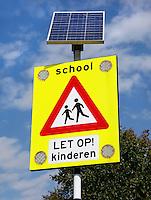 Bord om te waarschuwen voor overstekende kinderen. Bovenop het bord staat een zonnepaneel