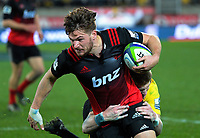 Jordie Barrett tries to stop George Bridge during the Super Rugby match between the Hurricanes and Crusaders at Westpac Stadium in Wellington, New Zealand on Saturday, 15 July 2017. Photo: Dave Lintott / lintottphoto.co.nz