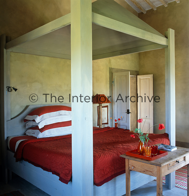 The large wooden bed has been painted a light shade of grey and has red and white bed linen