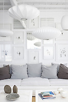 Retro style pendant lights hang above a white sofa and coffee tables. The austere white is set off by cushions in shades of grey.