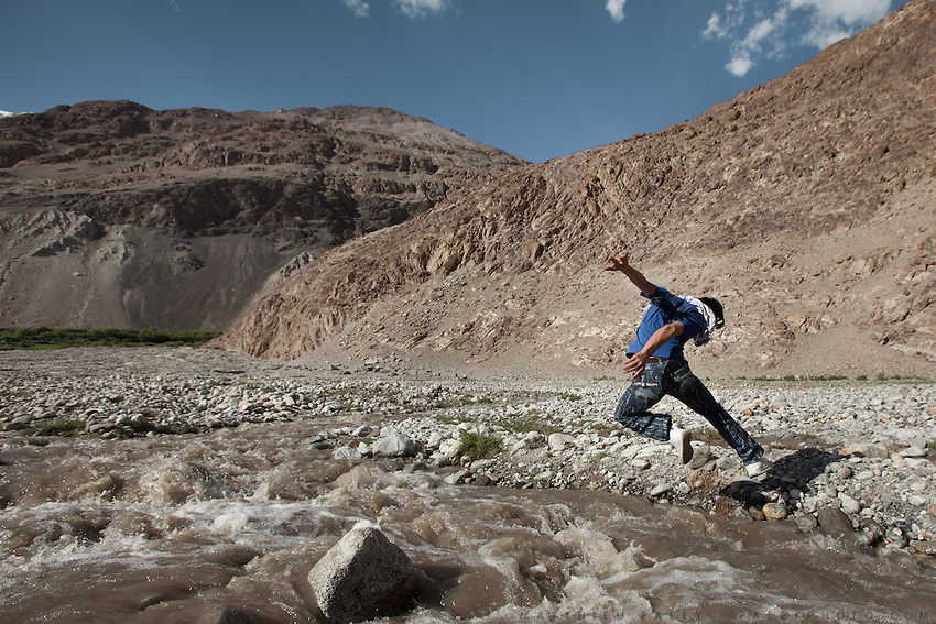 A young Wakhi man jumps over a river. Driving up from Ishkashim town to Sarhad village, the end of the road in the Wakhan corridor, Afghanistan.