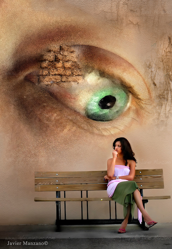 23 year-old, sitting on a bench, with graffitti of an eyeball behind her.