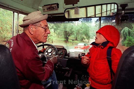 Kid talks to bus driver on school bus.<br />