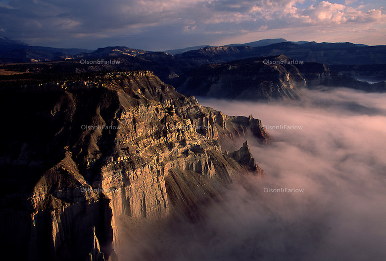 Morning fog fills a canyon below sheer sandstone cliffs of Grand Staircase Escalante National Monument in Utah.  The rugged unique terrain of arches, plateaus and colorful canyon walls covers 1.7 million acres and was the first monument named under the BLM by President Bill Clinton in 1996.