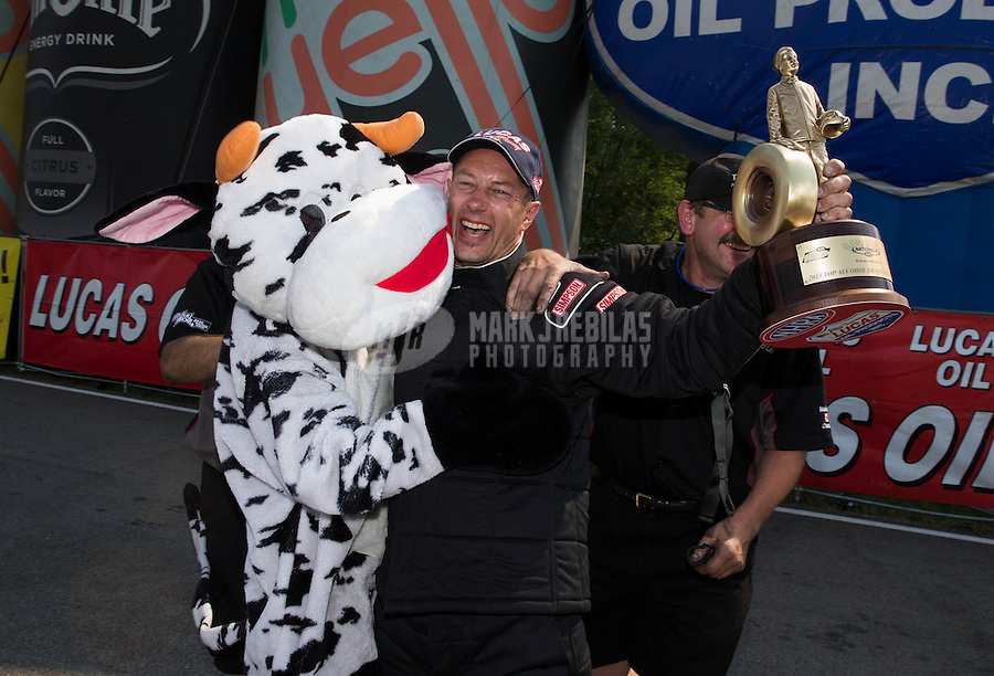 Aug. 18, 2013; Brainerd, MN, USA: NHRA top alcohol dragster driver Gord Gingles celebrates with crew and a cow after winning the Lucas Oil Nationals at Brainerd International Raceway. Mandatory Credit: Mark J. Rebilas-