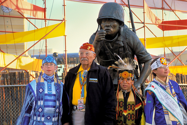 Navajo Code Talker and youth dressed in pow wow regalia stand next to a statue honoring the Navajo Code Talkers of WWII