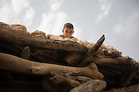 Morocco - Tidzi - Amina Hammoush's son Elia plays on the rooftop of their house while his mother prepares the fire to roast the argan nuts.