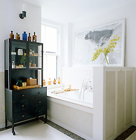 In the master bathroom a large photographic print by John Divola hangs above the bath and a vintage pharmacy cabinet displays a collection of antique bottles