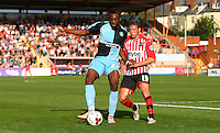 Gozie Ugwu of Wycombe Wanderers holds off Lee Holmes of Exeter City  during the Sky Bet League 2 match between Exeter City and Wycombe Wanderers at St James' Park, Exeter, England on 26 September 2015. Photo by Pinnacle Photo Agency.