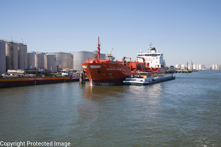 Chemical oil bulk carrier ship 'Crystal Topaz' next to storage tanks, Port of Rotterdam, Netherlands