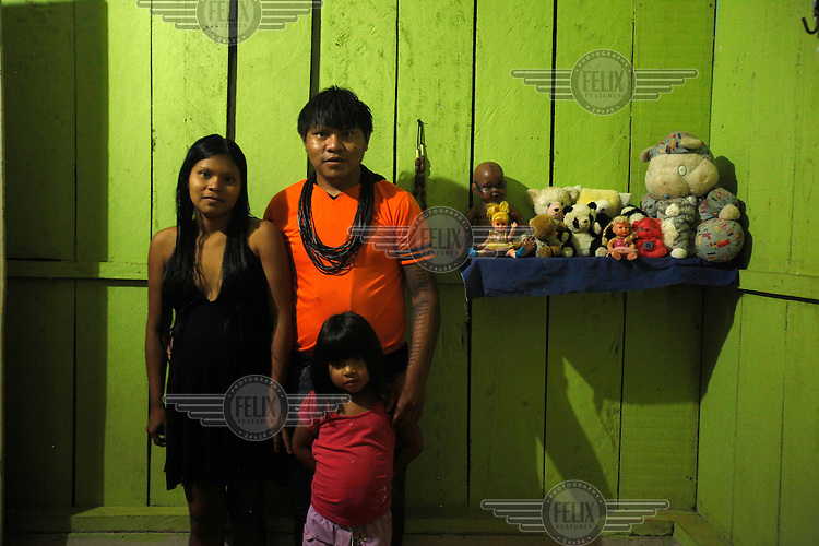 Roni Surui of the Surui (Paiter) tribe with his wife and daughter in the village of Lapetanha, in the Brazilian Amazon. The Surui had had no contact with the world outside their Amazonian homelands until, in 1969, a road was built through their territory. At the time there were around 5000 Surui but within three years disease had wiped out all but 290 Surui...