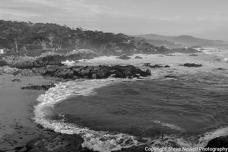 """The Ocean"" Black and White. Pacific Ocean on 17 Mile Drive- Pebble Beach, California. Sunset on the Pacific Ocean.  The Cypress trees lining the coastal rocks as the waves crash onto the beach just south of Carmel on a stretch of highway named 17 Mile Drive. This is one of the best stretches of Coastal Highway in all of California.  There is a lot more than just Golf at Pebble Beach. In this version I made an adjustment to smooth out the texture of the rocks and cypress trees that give this photograph a more artistic perspective. I think it's quite unique looking."