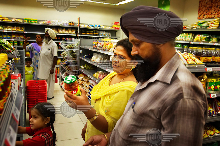 Sikh shoppers on their first trip to a Reliance Fresh store in Jalandhar. Reliance Fresh is the largest in a new wave of western style super markets that have recently opened across India. Called 'formal retail' the stores are a break from small corner stores and open markets. They feature air conditioning, bright lights and a wide variety of products offered uniformly at all stores. Their openings have been met occasionally by violent protest and several stores were burned by farmers and traders who see them as a threat.