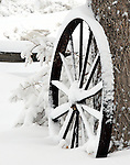 A rustic steel wagon wheel in the winter snow.