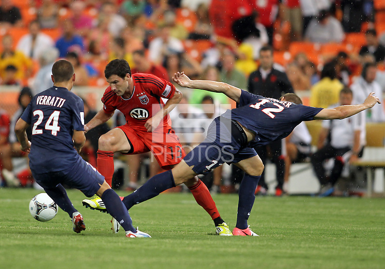 WASHINGTON, DC - July 28, 2012:  Chris Pontius (13) of DC United pushes away from Marco Verratti (24) and Mathieu Bodmer (12) of PSG (Paris Saint-Germain) in an international friendly match at RFK Stadium in Washington DC on July 28. The game ended in a 1-1 tie.