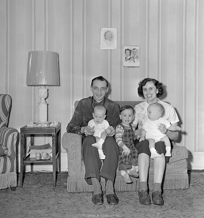 A family, including a child and two twin babies pose for the camera. Circa 1950.