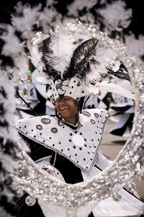A woman in black and white laughs while dancing in the street parade for the ZomerCarnaval (Summer Carnival) in Rotterdam, the Netherlands. The street parade is the colorful high point of the Rotterdam carnival. It is a tropical themed parade with over 2000 participants and travels 6km through the center of Rotterdam.
