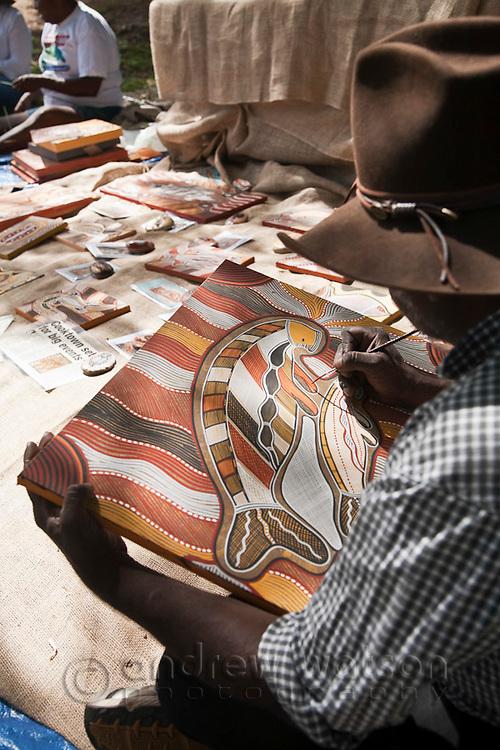 Indigenous man painting traditional artwork.  Cooktown, Queensland, Australia