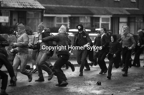Belfast, Northern Ireland. 1981<br /> The Troubles charging Catholic rioting balaclava disguised youths throw petrol bombs at the British army in the Falls Road.