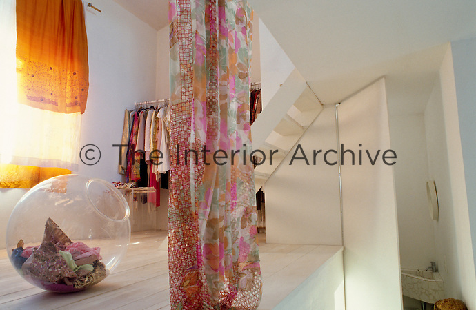 A rack of Carolyn Quartermaine's clothes is stored on a mezzanine floor of her open-plan house