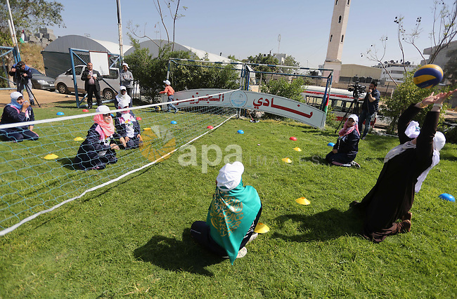 Disabled Palestinians play sitting volleyball during a local sports championship organized by Al Jazeera club in Gaza City April 7, 2016. Photo by Mohammed Asad