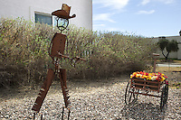 USA. Arizona state. Kearny town. A rusty metal sculpture of a cowboy holding two Colt pistols stands in the garden of a private house. The Colt Single Action Army which is also known as the Single Action Army, SAA, Model P, Peacemaker, M1873, and Colt .45 is a single-action revolver with a revolving cylinder holding six metallic cartridges. It was designed for the U.S. government service revolver trials of 1872 by Colt's Patent Firearms Manufacturing Company – today's Colt's Manufacturing Company – and was adopted as the standard military service revolver until 1892. The Colt SAA has been offered in over 30 different calibers and various barrel lengths. Its overall appearance has remained consistent since 1873. The revolver was popular with ranchers, lawmen, and outlaws alike, but as of the early 21st century, models are mostly bought by collectors and re-enactors. Its design has influenced the production of numerous other models from other companies. A firearm is a portable gun, being a barreled weapon that launches one or more projectiles often driven by the action of an explosive force. Most modern firearms have rifled barrels to impart spin to the projectile for improved flight stability. The word firearms usually is used in a sense restricted to small arms (weapons that can be carried by a single person). The right to keep and bear arms is a fundamental right protected in the United States by the Second Amendment of the Bill of Rights in the Constitution of the United States of America and in the state constitutions of Arizona and 43 other states. 31.01.16 © 2016 Didier Ruef