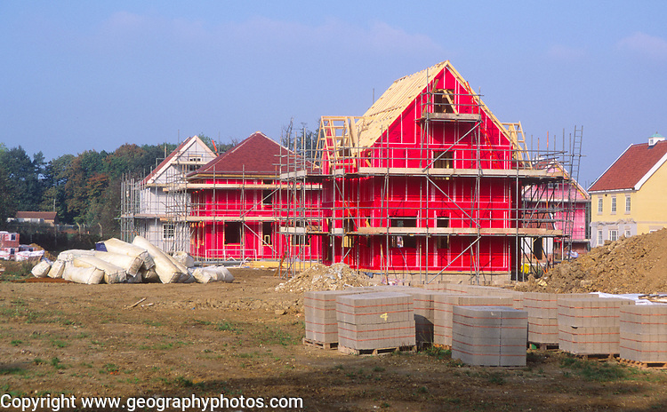 ATBK35 Building site with red cladding and scaffolding as new houses are built Rendlesham Suffolk