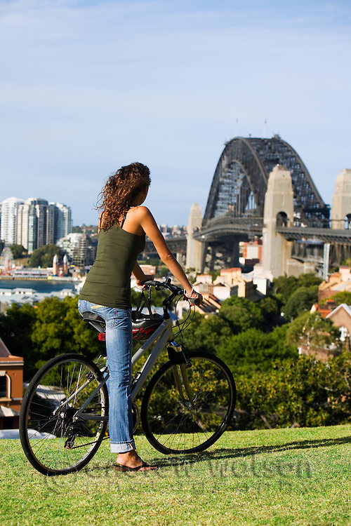 A cyclist looks out over Sydney harbour from Observatory Hill.  The Rocks,  Sydney, New South Wales, AUSTRALIA.