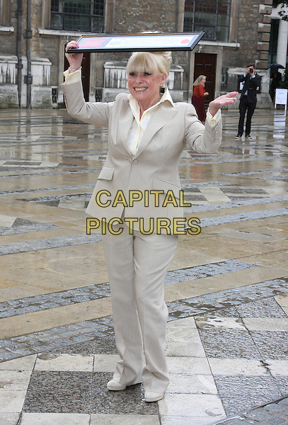 BARBARA WINDSOR.attends a photocall after receiving the Freedom of the City of London at the Guildhall, London, England, UK,.August 4th 2010.full length cream beige suit shirt jacket fringe holding over head raining trousers trouser hand .CAP/JIL.©Jill Mayhew/Capital Pictures