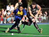 NZ captain Phil Burrows is tackled by Muhammad Ahmin Rahim during the international hockey match between the New Zealand Black Sticks and Malaysia at Fitzherbert Park, Palmerston North, New Zealand on Sunday, 9 August 2009. Photo: Dave Lintott / lintottphoto.co.nz
