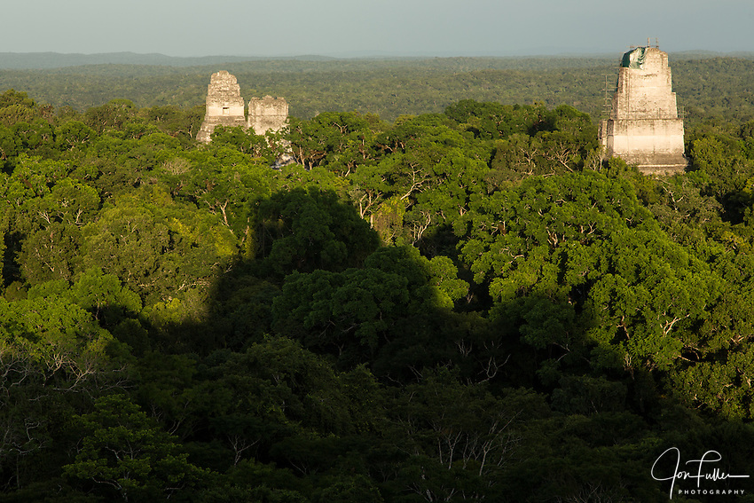 View at sunset of Temples I, II and III from Temple IV in the Mayan archeological site of Tikal National Park, Guatemala.  The shadow of Temple IV is in the forground.  A UNESCO World Heritage site since 1979.