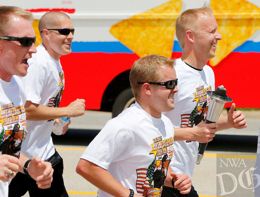 NWA Democrat-Gazette/DAVID GOTTSCHALK - 5/18/15 - Corporal Shawn Allen,  with the Fayetteville Police Department, carries the torch south on College Avenue after leaving the transition area at Centennial Bank on E. Joyce Boulevard during the Law Enforcement Torch Run for Special Olympics Monday May 18, 2015. Torches began their journeys in the four corners of the state on Monday morning and will be relayed by law enforcement agencies to the opening ceremony of the 2015 Special Olympics Arkansas Summer Games on Thursday at Harding University in Searcy.
