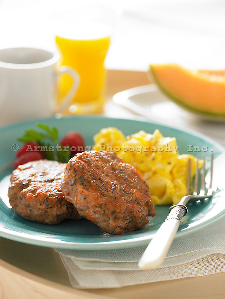 Breakfast plate with salmon patties, scrambled eggs, fresh fruit, orange juice, coffee