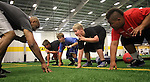 SIOUX FALLS, SD - JULY 2:  Rachman Crable, left, shows the proper stance for a defensive lineman to, from left, Luke Schuldt,  Charlie Mickelson, Jon Rames, and Titus Benton during drills at the Riggs Football Academy Tuesday night at the Sanford Fieldhouse. (Photo by Dave Eggen/Inertia)