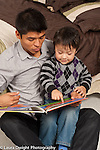 Two year old toddler boy with father read to