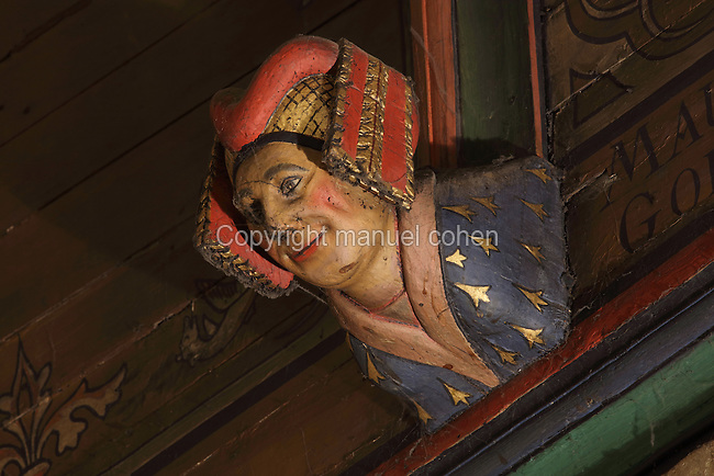 Carved and painted roof bracket with head of a smiling woman wearing traditional costume, architectural detail of the painted wooden ceiling in the shape of a boat's hull, in the Salle des Povres or Room of the Poor, almost 50m long, in Les Hospices de Beaune, or Hotel-Dieu de Beaune, a charitable almshouse and hospital for the poor, built 1443-57 by Flemish architect Jacques Wiscrer, and founded by Nicolas Rolin, chancellor of Burgundy, and his wife Guigone de Salins, in Beaune, Cote d'Or, Burgundy, France. The hospital was run by the nuns of the order of Les Soeurs Hospitalieres de Beaune, and remained a hospital until the 1970s. The building now houses the Musee de l'Histoire de la Medecine, or Museum of the History of Medicine, and is listed as a historic monument. Picture by Manuel Cohen